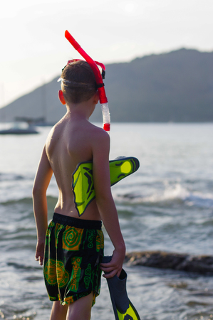 young boy with snorkeling equipment at beach during summer vacation Stock Photo