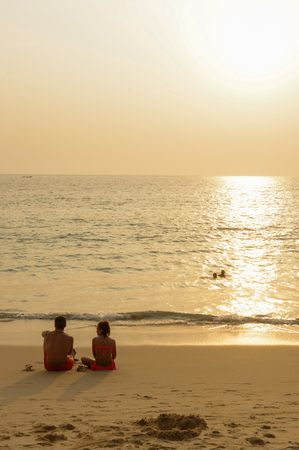 scenic beautiful romantic sunset over sea with people silhouette in sitting in water and enjoy the evening orange sun at adaman ocean, Patong Beach Phuket island, Thailand Stock Photo