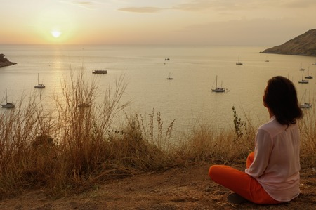 a Young girl sitting in yoga lotus meditation position in front to seaside on the rocks an watching the sun goes down in a golden hour. sunset over sea. Stock Photo