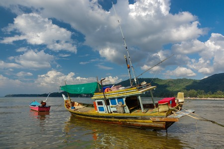 Thai old fishing small boat at low tide in the shallows.