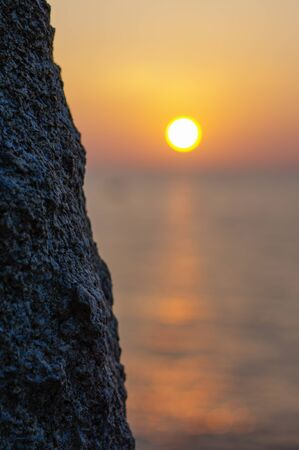 a Vivid orange sunset over water with rock silhouettes. Thailand, Phuket Island.