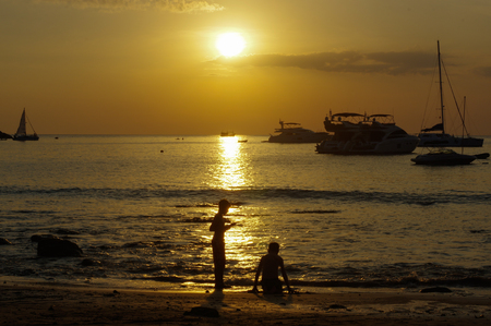 a silhouette of a boys play with sand at sunset and boat on the sea
