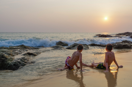 two boys sitting on the beach by the sea and enjoy the sunset behind the rocks and the sea. Thailand, Phuket island. Surin
