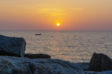 a Vivid orange sunset over water with a boat and rock silhouettes. Thailand, Phuket Island.