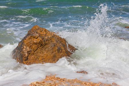 stone wash: waves splashing rock Stock Photo