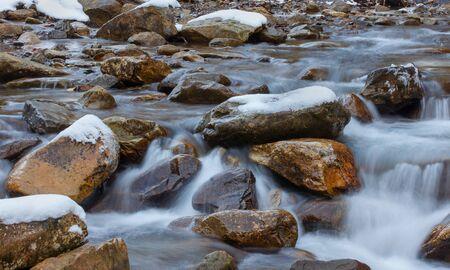 big stone in frozen water Stock Photo