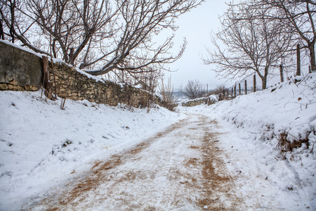 winter rural scenery, dirty country road covered by snow