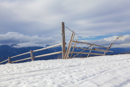 wooden fence and gate on the snowy hill