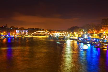 Río Sena y puente por la noche en París