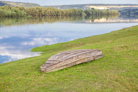 upside-down boat on the river shore Stock Photo