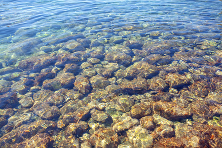 stones under transparent sea water