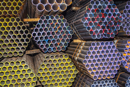stockpiled industrial pipes , metallic background