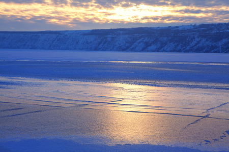 winter scenery with sunset and frozen lake
