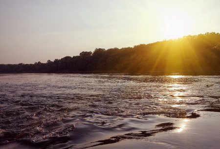 flowing water surface and sun going down Stock Photo