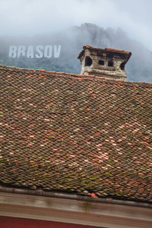 inscription Brasov on the mountain , old tiled roof in Romania Stock Photo