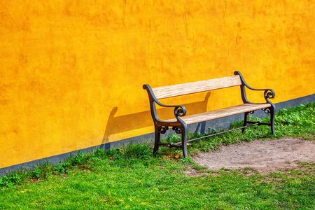 wooden bench near yellow wall Stockfoto