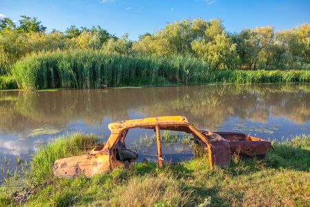 rusty car frame in the swamp water