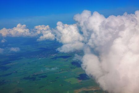 flight through the clouds and over green fields 写真素材