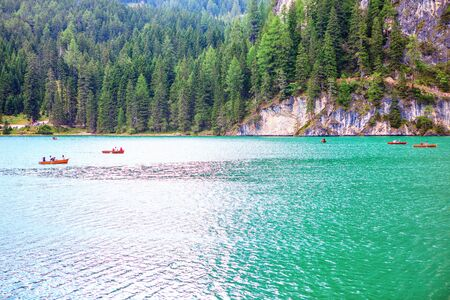 wooden boats sailing on Lago di Braies in Italy