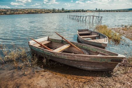 two wooden fishing boats on the river shore