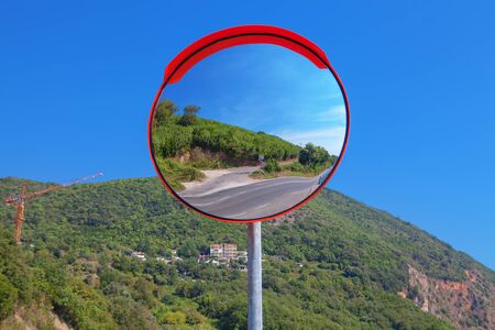 green mountain reflection in road mirror