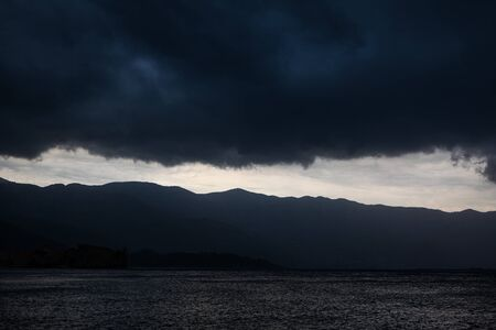black dramatic clouds over the mountains and the sea Stock Photo