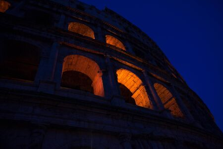 part of ancient Colosseum illuminated in the night