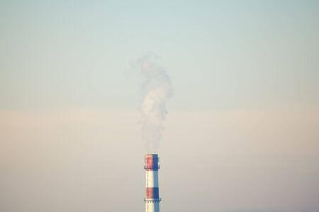 Industrial plant with smokestack on the sky
