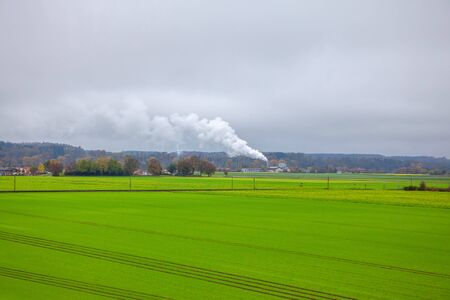 ecological image with green field and white smoke from the chemical plant