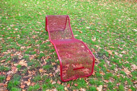 red chair in the park on the green meadow