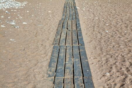 wooden footpath on the sandy beach