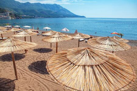 tropical beach with hay umbrellas
