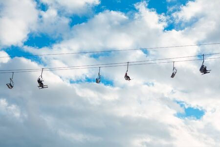 rope with skiers against blue sky