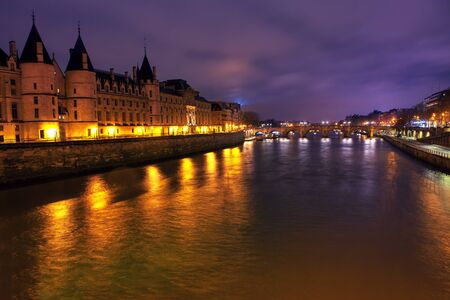 Night view of Conciergerie and Seine river in Paris Stock Photo