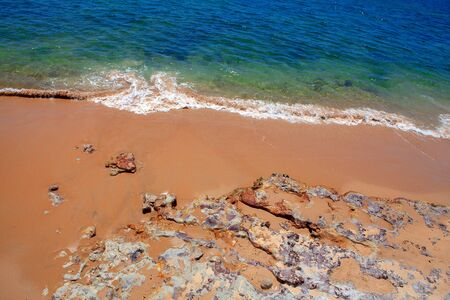ocean waves and sandy beach with rocks Stock Photo