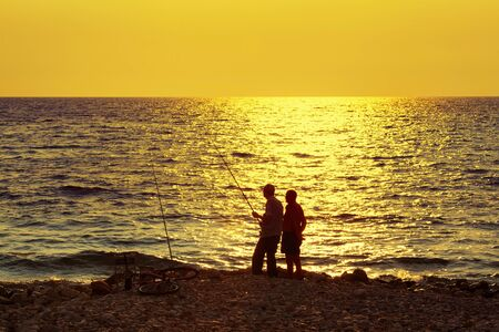 two old man fishing in the evening