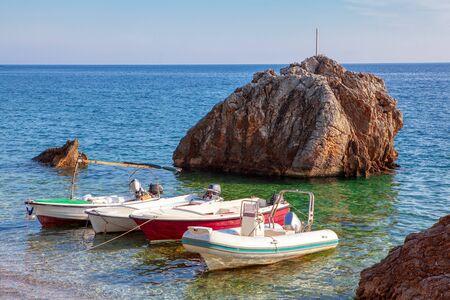 bateaux blancs amarrés à la côte rocheuse