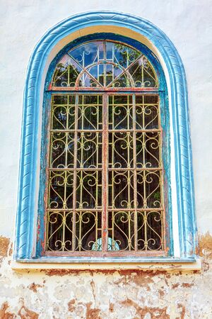 stucco window with arch and grate