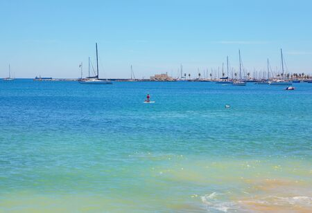 Girl on a paddle board . Harbour with yachts . Atlantic Ocean Berth