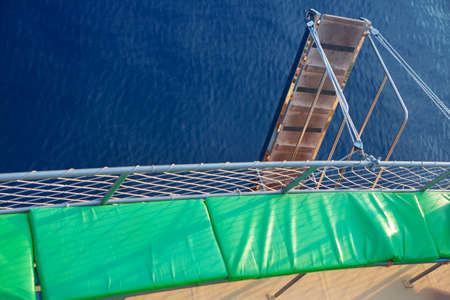 Wooden ship ladder .  Blue sea background . Touristic ship with sun loungers