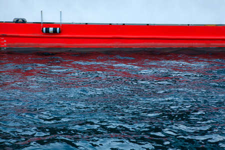 part of the ships hull that is submerged in water . Red painted ferry board