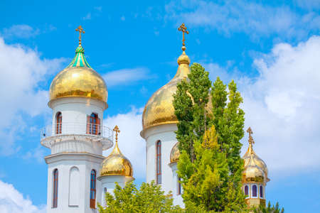 Church with Golden Domes . Religious Cross on the Cupola Top Фото со стока