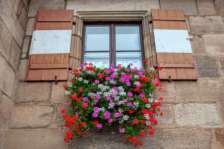 Window with shutters and flowers . Exterior flower bed under the window Archivio Fotografico
