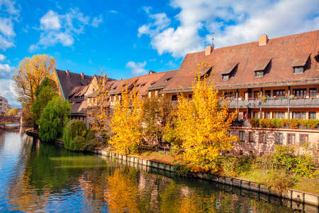 Residential district situated at the riverside . Autumn Scenery in German City . House with attics situated at the river shore 写真素材