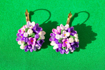 Flower shaped earrings for summer fashion . Green Background 写真素材