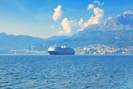 Travel around the world by cruise liner . Scenery with blue sea and coastal mountains