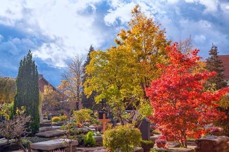 Autumn in cemetery . Graveyard with colorful trees in the fall season . Johannisfriedhof Cemetery in Nuremberg