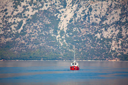 Red yacht on the bay with mountains on background Stok Fotoğraf - 154905882
