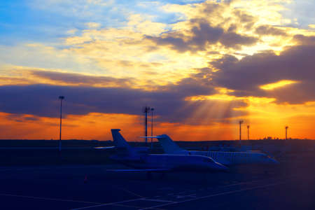 Sunset over the airport . Planes in the twilight