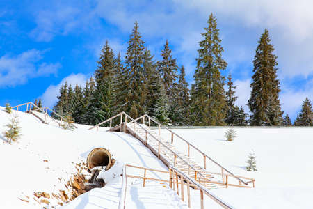 Fir Trees on the snowy hill . Wooden Staircase in the winter Standard-Bild